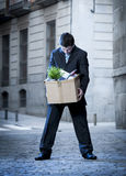 Frustrated business man on street fired carrying cardboard box Royalty Free Stock Images