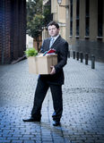 Frustrated business man on street fired carrying cardboard box. Frustrated business man fired in crisis carrying cardboard box on street Royalty Free Stock Images