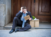 Frustrated business man on street fired carrying cardboard box Stock Photo