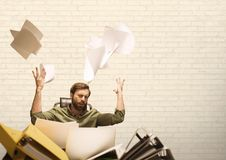 Frustrated business man throwing paper against white background. Digital composite of Frustrated business man throwing paper against white background Royalty Free Stock Photo