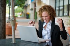 Frustrated Business Woman. Young business woman, crushing a coffee cup in one hand, extremely distraught and frustrated with her laptop computer Royalty Free Stock Photo