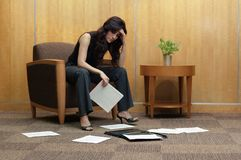 Frustrated Business Woman. Frustrated business women in office lobby, with paper mess royalty free stock photo