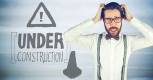 Frustrated business woman against brown background and construction graphic. Digital composite of Frustrated business woman against brown background and Royalty Free Stock Photography