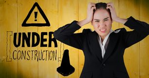Frustrated business woman against yellow wood panel and construction graphic. Digital composite of Frustrated business woman against yellow wood panel and stock photos