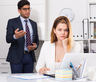 Frustrated business woman with angry chief. Frustrated business women sitting at office desk on background with angry chief stock photography