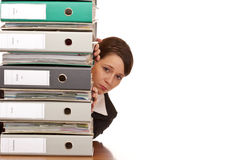 Frustrated business woman behind folder stack Stock Photography