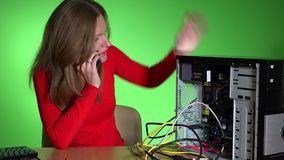Frustrated business woman calling computer support service. Office girl sitting near broken desktop pc. Green wall background. Static closeup shot. 4K UHD stock footage