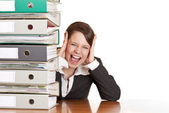 Frustrated business woman cries near folder stack. Frustrated business woman cries in office behind behind a folder stack. Isolated on white background Royalty Free Stock Photo