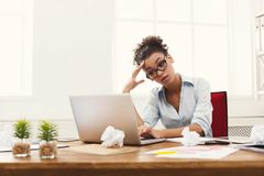 Frustrated business woman with headache at office. Deadline stress concept - sad african-american business woman sitting at desktop in office and holding hand on Royalty Free Stock Image