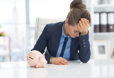 Frustrated business woman with piggy bank. On desk Stock Photography