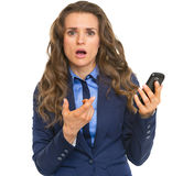 Frustrated business woman pointing on cell phone Royalty Free Stock Photos