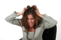 Frustrated Business Woman Pulling Her Hair Out 2. Frustrated executive business woman with a troubled expression sitting in her office chair pulling her hair out Stock Images