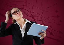 Frustrated business woman with tablet against maroon background and graph Royalty Free Stock Image