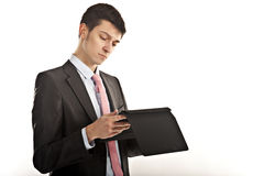 Frustrated businessman biting his computer tablet. This is an image of a young smartly dressed man biting his computer tablet royalty free stock photos