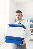 Frustrated businessman carrying boxes Royalty Free Stock Photo