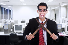 Businessman cutting his neck with a scissor. Frustrated businessman cutting his neck with a scissor in a workplace Stock Photography