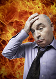 Frustrated businessman with hand on head standing against fire Stock Image