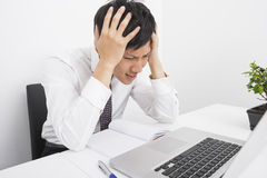 Frustrated businessman with head in hands sitting at desk in office Stock Photography