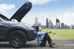 Frustrated businessman leaning on broken down car royalty free stock photos