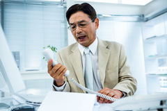 Frustrated businessman looks his phone. In his office Royalty Free Stock Photos