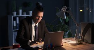 Frustrated businessman at night office. Businessman closing laptop in frustration late at night office stock footage