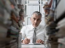 Frustrated businessman and piles of paperwork. Frustrated tired businessman working in the office and stacks of paperwork on the desk Stock Photography