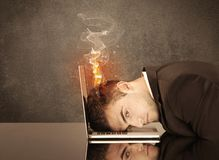 Sad business person`s head catching fire. A frustrated businessman resting his head on a keyboard and shouting with his hair on smoke, catching fire Stock Photography