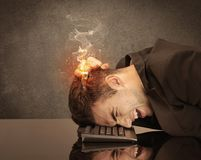 Sad business person`s head catching fire. A frustrated businessman resting his head on a keyboard and shouting with his hair on smoke, catching fire Royalty Free Stock Photo