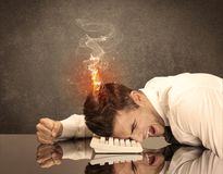 Sad business person`s head catching fire Royalty Free Stock Image