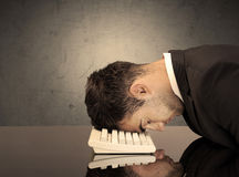 Frustrated businessman's head on keyboard Royalty Free Stock Images