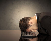 Frustrated businessman`s head on keyboard Stock Images