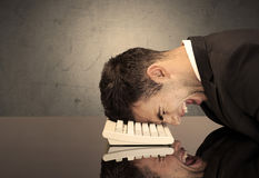 Frustrated businessman`s head on keyboard Royalty Free Stock Photos