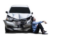 Frustrated businessman sits next to damaged car Royalty Free Stock Photography