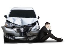 Frustrated businessman is sitting near damaged car Royalty Free Stock Image