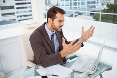 Frustrated businessman using laptop in office Stock Photography