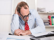 Frustrated businessman wearing glasses sitting at desk with head Royalty Free Stock Images