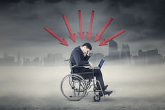 Frustrated businessman with wheelchair and arrow Stock Image