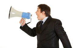 Frustrated businessman yelling through megaphone. Frustrated young businessman yelling through megaphone isolated on white Stock Image