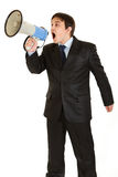 Frustrated businessman yelling through megaphone. Frustrated young businessman yelling through megaphone isolated on white Royalty Free Stock Images