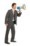Frustrated businessman yelling through megaphone. Full length portrait of frustrated modern businessman yelling through megaphone on white Stock Image