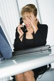 Frustrated businesswoman. Caucasian businesswoman with hand to head and frustrated expression at computer desk on telephone Stock Photography