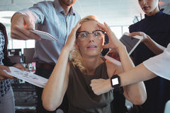 Frustrated businesswoman amidst team holding technologies Stock Photos
