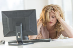Frustrated Businesswoman With Hands In Hair Sitting At Desk Stock Image
