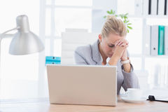 Frustrated businesswoman with head in hands Royalty Free Stock Photography