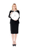 Frustrated businesswoman holding a clock Stock Photos