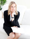Frustrated businesswoman holding a paper on a sofa. Frustrated businesswoman holding a paper sitting on the sofa in the office Stock Photos
