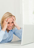 Frustrated businesswoman looking at her notebook Stock Images
