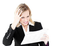 Frustrated businesswoman looking at a newspaper Royalty Free Stock Photo