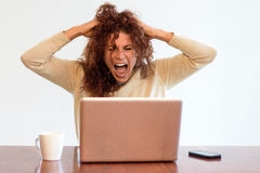 Frustrated businesswoman screaming at her laptop Royalty Free Stock Photography