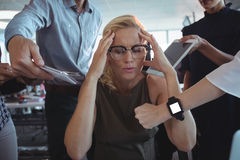 Frustrated businesswoman sitting amidst team holding technologies. At office Stock Photos